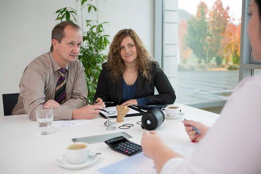 Mann und zwei Frauen sitzen am Verhandlungstisch